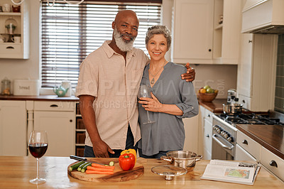 Buy stock photo Portrait of an affectionate and happy senior couple preparing dinner together inside their kitchen
