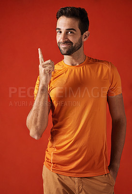 Buy stock photo Studio shot of a handsome young man pointing up against a red background