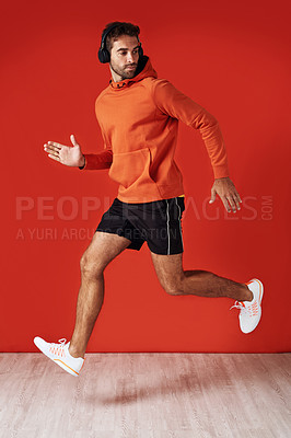 Buy stock photo Studio shot of a handsome young man listening to music while exercising against a red background