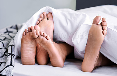 Buy stock photo Cropped shot of an unrecognizable couple's feet poking out from under their bed sheets