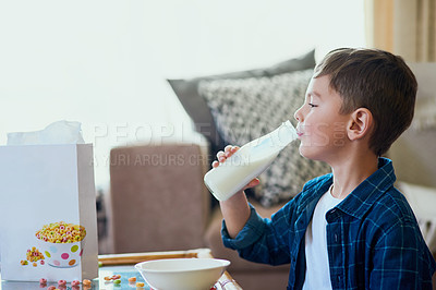 Buy stock photo Shot of an adorable little boy drinking milk and having cereal at home