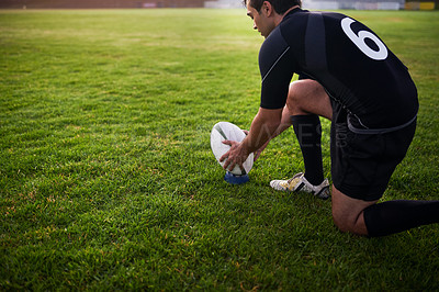 Buy stock photo Cropped shot of a handsome young sportsman crouching alone during rugby practice in a sports club