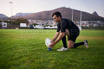 Buy stock photo Full length shot of a handsome young sportsman crouching alone during rugby practice in a sports club