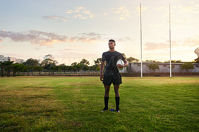 Buy stock photo Full length shot of a handsome young sportsman standing alone and holding a rugby ball before an early morning practice