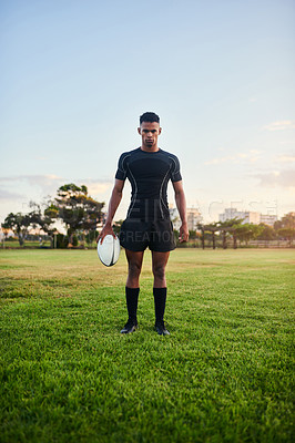 Buy stock photo Full length portrait of a handsome young sportsman standing alone and holding a rugby ball before an early morning practice