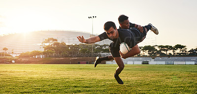 Buy stock photo Full length shot of two handsome sportsmen playing rugby during a training session during the day
