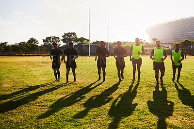 Buy stock photo Full length shot of a diverse group of sportsmen warming up before playing rugby during the day