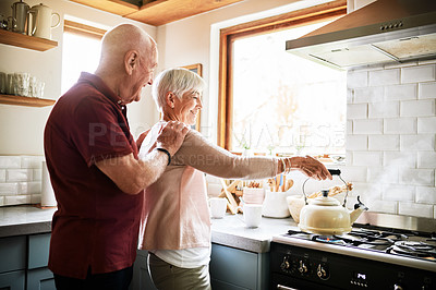 Buy stock photo Cropped shot of an affectionate senior couple standing together in the kitchen of their home during the day