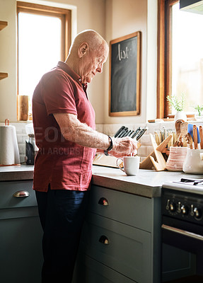 Buy stock photo Cropped shot of a handsome senior man standing alone in his kitchen and making a cup of coffee