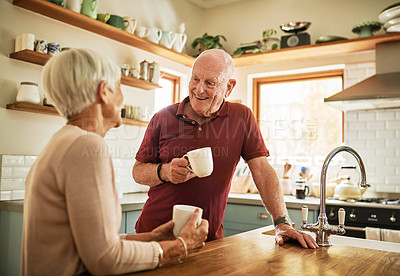 Buy stock photo Cropped shot of a happy senior couple bonding together over a cup of coffee in their kitchen at home