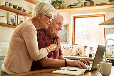 Buy stock photo Cropped shot of a happy senior couple using a laptop in their kitchen during the day