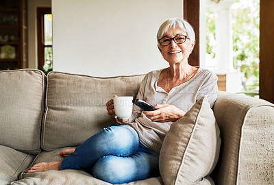 Buy stock photo Full length portrait of an attractive senior woman sitting alone on her sofa and holding a cup of coffee