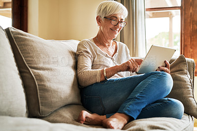 Buy stock photo Full length shot of an attractive senior woman sitting alone in her living room and using a tablet