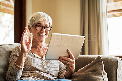 Buy stock photo Cropped shot of an attractive senior woman sitting alone on her sofa and using a tablet for a video call