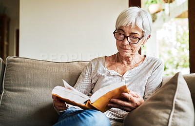 Buy stock photo Cropped shot of a senior woman sitting alone on her sofa and reading through a cookery book