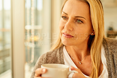 Buy stock photo Shot of an attractive mature woman enjoying a cup of coffee at home