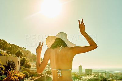 Buy stock photo Rearview shot of a young woman spending the day by the pool