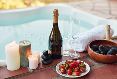 Buy stock photo Cropped shot of strawberries and champagne laid out among hot stones and hot compresses at a spa during the day