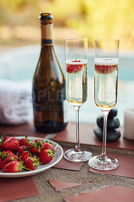 Buy stock photo Cropped shot of strawberries floating in glasses of champagne at a spa during the day