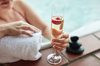 Buy stock photo Cropped shot of an unrecognizable woman sitting in a jacuzzi alone and enjoying a glass of champagne at a spa