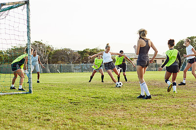 Buy stock photo Full length shot of a young sportswoman scoring a goal for her team during a soccer match outdoors