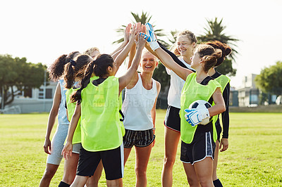 Buy stock photo Full length shot of a team of female soccer players joining hands together to high five each other outdoors on the filed