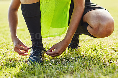 Buy stock photo Cropped shot of an unrecognizable female soccer player lacing up her boots outdoors on the field