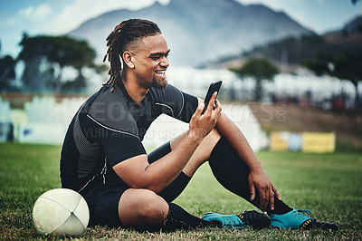 Buy stock photo Full length shot of a handsome young rugby player using a smartphone while sitting in the playing field during the day