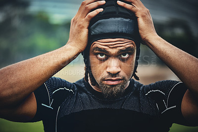 Buy stock photo Cropped shot of a handsome young rugby player adjusting his headgear while standing on the field during the day