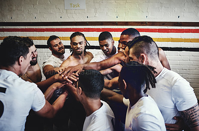 Buy stock photo Cropped shot of a group of handsome young rugby players standing together in a huddle in a locker room
