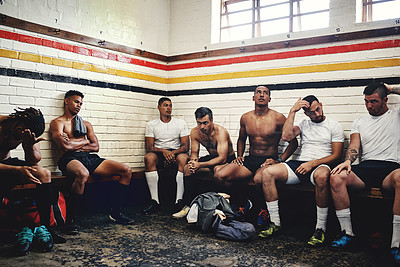Buy stock photo Cropped shot of a group of handsome young rugby players sitting together in a locker room during the day