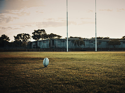 Buy stock photo Still life shot of a rugby ball on an empty rugby field during the early hours of the morning at a sports club