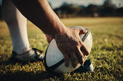 Buy stock photo Cropped shot of an unrecognizable rugby player preparing for a kick on the field during the day