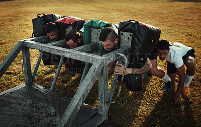 Buy stock photo Full length shot of a group of young rugby players training with tackle bags on the field during the day