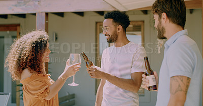 Buy stock photo Shot of a group of young friends toasting with drinks during a barbecue at home