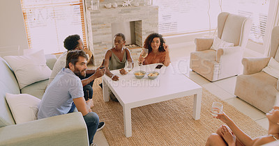 Buy stock photo Shot of a group of young friends having beers and snacks in the living room at home