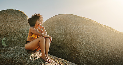 Buy stock photo Full length shot of an attractive young woman sitting on a rock and posing during a day out at the beach