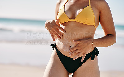 Buy stock photo Cropped shot of an unrecognizable woman standing alone and rubbing sunblock on her tummy while on the beach