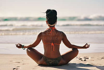 Buy stock photo Full length shot of an unrecognizable woman sitting alone on the beach and meditating