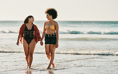 Buy stock photo Full length shot of two attractive young friends standing together and holding hands while walking on the beach