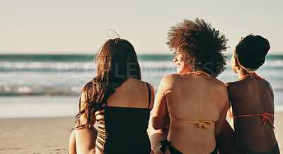 Buy stock photo Rearview shot of three female friends spending the day at the beach