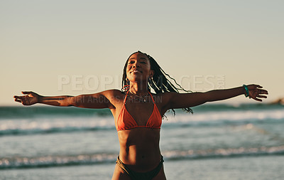 Buy stock photo Shot of a young woman spending time at the beach at sunset