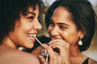 Buy stock photo Cropped shot of two friends sharing a drink using metal straws while standing outdoors