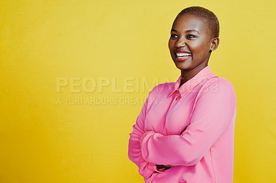 Buy stock photo Cropped shot of an attractive and confident young woman posing with her arms folded against a yellow background