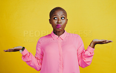 Buy stock photo Cropped shot of an attractive young woman looking curious and indecisive against a yellow background