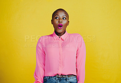 Buy stock photo Cropped shot of an attractive young woman looking curious and surprised in studio against a yellow background