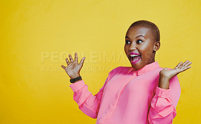 Buy stock photo Cropped shot of an attractive young woman looking cheerful and surprised in studio against a yellow background