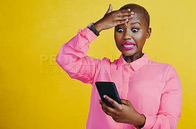 Buy stock photo Cropped shot of an attractive young woman panicking and feeling anxious while using her cellphone against a yellow background