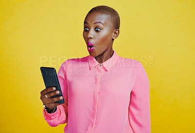 Buy stock photo Cropped shot of an attractive young woman looking surprised while using her cellphone in studio against a yellow background