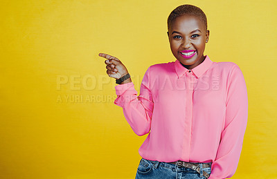 Buy stock photo Portrait of an attractive young woman pointing left in studio against a yellow background